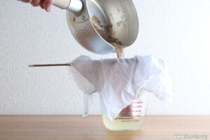 ザルにふきんを敷いてこします。